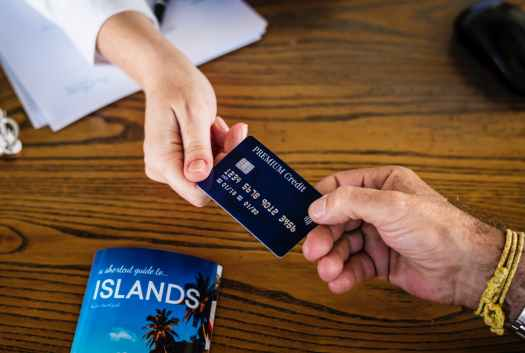 two persons holding premium credit card